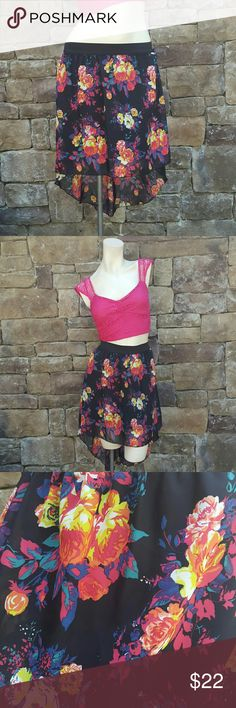 NWT Floral Hi-Low Skirt This is a beautiful and bright Hi-Low Skirt: shorter in the front, longer in the back. There is an elastic waist band so it can be worn Hi-waisted or down around the hips. The bottom of the skirt is a flowy chiffon-like material. The background color is black and the floral print has hot pink, orange, yellow, purple, and teal. Never worn, with tags attached. Charlotte Russe Skirts High Low
