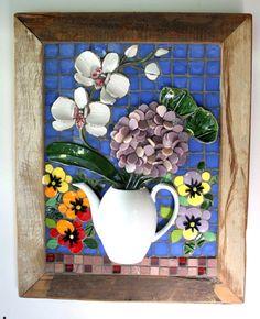 A delicadeza e beleza de um arranjo floral contendo uma orquídea da espécie Phalaenopsis, uma hortênsia e um buquê de amor perfeito, com uma moldura rústica em madeira de demolição, resulta num quadro harmonioso e cheio de personalidade. Utilizando a técnica francesa Picassiette (mosaico com lou...