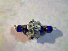 This pin has a silvery gray keishi pearl cluster in the center, with vibrant deep blue Czech glass beads at each end. Each pearl is attached with a hand-knotted head pin with a blue seed bead center. This pin has a sterling silver frame, and is approximately 1.75 inches long. This style of pin works well on shawls, scarves, and hats.