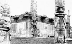 """Chief Wiah's Monster House and two of the memorial poles which stood out front. This is one of the clearest photographs of the memorial pole on the left, detailing the cumulous cloud figure, often called """"Cloud Woman,"""" with the large recurved beak."""