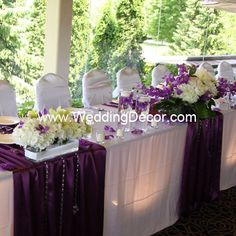 Wedding Decor  Head Table - white linens, purple runners, hydrangea and purple dendrobium orchids in glass vases with floating candles