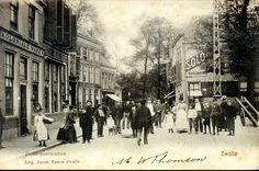 """Gezicht op de Diezerpoortenplas in de richting van de Stenen pijp, ca. 1900. De huizen aan de linkerzijde van de straat (winkel met opschrift """"Koloniale Waren"""") zijn in de periode 1975-1990 gerenoveerd en weer bewoonbaar gemaakt. Na het tweede huis is de toegang tot de Thorbeckegracht. Op Diezerpoortenplas 32 (rechts) staat muurreclame voor """"Jurgens Solo Margarine"""" en """"Bruinkool"""" (Dierzerpoortenplas 32). Op het pleintje staan een straatlantaarn en een ijzeren telefoonpaal (geplaatst vanaf…"""
