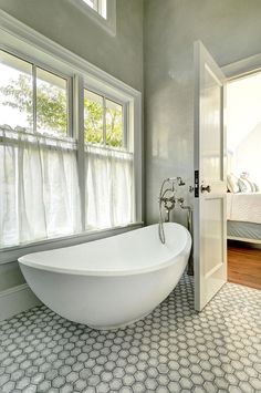 Bathroom Freestand bath. The bathroom features walls clad in gray marble, windows dressed in gray pinstripe cafe curtains and a modern egg shaped tub paired with a floor-mount vintage style tub filler. Bathroom freestanding bath ideas. #Bathroom #Bath #FreestandingBath John Hummel and Associates.