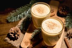 Homemade traditional Christmas eggnog drinks with ground nutmeg, cinnamon and decorating items on wood table, preparing for celebrating festive holiday season Eggnog Drinks, Spiced Eggnog, Eggnog Recipe, How To Clean Metal, Punch Bowls, Holiday Drinks, Christmas Traditions, Christmas Recipes