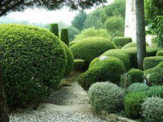 A beautiful sculpted garden frames a gravel path