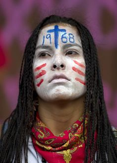 A student with her face painted attends a march marking the 44th anniversary of the Tlatelolco massacre in Mexico City, Tuesday Oct. 2, 2012. On Oct. 2, 1968, soldiers opened fire against a student demonstration in Mexico City's Tlatelolco Plaza just before the capital hosted the Olympics. Official reports said 25 people were killed, but human rights activists say as many as 350 may have died. [Credit : Eduardo Verdugo/AP]