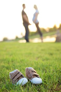Maternity pic - baby shoes in focus in foreground, couple out of focus in background