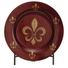 """Tuscan Fleur-de-lis Glass Charger Plate with Metal Stand by Cheap-Chic Decor. $95.00. Dimensions: 19""""D (plate only). Tuscan Fleur-De-Lis Glass Charger Plate with Metal Stand. Burgandy Glass with Gold Fleur-de-lis Accents. In stock. Decorative Glass Plate with Metal Stand. Add a touch of style and color to your home with this Tuscan Old World charger plate and coordinating stand. The charger is a burgandy colored glass with gold painted fleur-de-lis accents. Metal stand is incl..."""