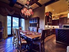 This Deer Valley dining room has herringbone flooring, exposed wood beam ceilings, dark cabinetry, high ceilings, colorful drapes, a classic hutch and colorful hanging light fixture.