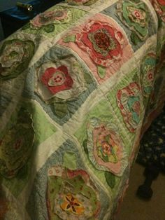 Sweet idea....i think ill piece the blocks and sashing then load it on my gammill and sew the flowers on???