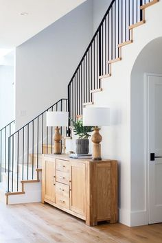Modern farmhouse foyer features a custom staircase with wrought iron stair railing - Home Bunch #Foyers
