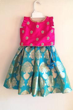 Beautiful pink silk top with a stunning hand embroidery paired with a turquoise blue brocade skirt. The top has flutter sleeves Girls Frock Design, Kids Frocks Design, Baby Frocks Designs, Baby Dress Design, Kids Lehanga Design, Kids Indian Wear, Kids Ethnic Wear, Baby Lehenga, Kids Lehenga