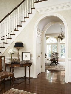 Stairs that wind to the right with doorway to living room underneath. Hallway would follow stairs to powder room and master suite
