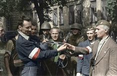 """Warsaw Uprising insurgents inspect war trophies including an armband with the name of """"Wiking"""", c1944 (Colorised by Tomek Iwanowski)"""