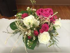 Table arrangement with roses, spray roses, twine, and wax flower accents by #SunshineFlorist
