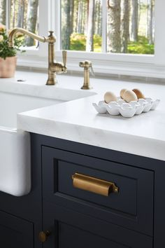 Marble Countertop: Honed Bianco Avian Marble Cabinet paint color: Midnight Oil by Benjamin Moore.