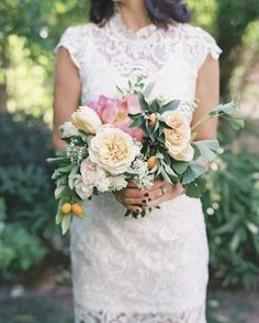 Bridesmaids at this Palm Springs wedding wore ivory dresses and carried bouquets by Hollyflora of garden roses, spirea, coral peonies, kumquats, and ginkgo.