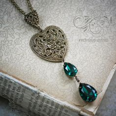 A gorgeous European style filigree heart with a Celtic influence suspends a double pear drop of Swarovski Emerald crystal pears.  Hung from an ornate, filigree bail then on a dainty 18