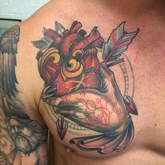 Tatuaje de una mano que sujeta un corazón situado en el pecho.