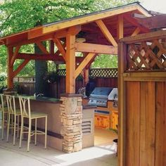 Covered outdoor kitchen with grill, sink, refrigerator, and more, with bar seating on the side. Great for entertaining!   11 fabulous outdoor kitchens   Living the Country Life   http://www.livingthecountrylife.com/homes-acreages/country-homes/11-fabulous-outdoor-kitchens/