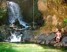 Use the rope swing to jump into the cold water pool fed from the mountain volcano at Kolekole Beach Park, Hawaii The Big Island
