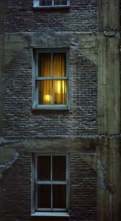 Night Windows:  Dark brick alley wall with lamp-lit window at night