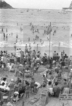 ESPAÑA-PLAYAS: San Sebastián, agosto 1956 Centenares de bañistas abarrotan la playa de La Concha junto a un cartel que p ...lafototeca.com