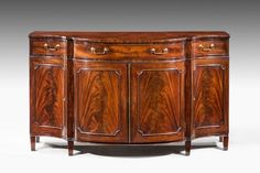 A very fine and original 18th Century Sideboard or Serpentine Commode attributed to Gillows of Lancaster, the beautiful figured four doors leaf matched, the top drawer section with very highly figured timbers, the top cross banded in mahogany, original square section gilt bronze handles on original square tapering supports.