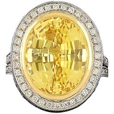 14.95 Carat Unheated GIA Cert Yellow Sapphire Diamond Ring. Platinum Cocktail Ring featuring a 14.95 Carat Oval Shape Mixed Cut Yellow Sapphire set in a Halo of Round Brilliant Cut Diamonds. Additional diamonds are accented down the shank and underside of the mounting.  c 2015
