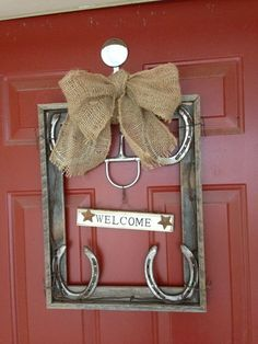 "Barn wood picture frame, horse shoes, barbed wire, a snaffle bit, welcome sign and burlap bow make a ""wreath"" for the front door and memories of my horse."