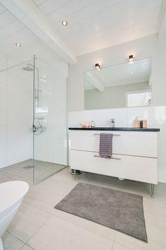 Mycket fräscht duschrum, helkaklat, glas och blanka ytor - och med träpanel i tak. Slingervägen i Haverdal.