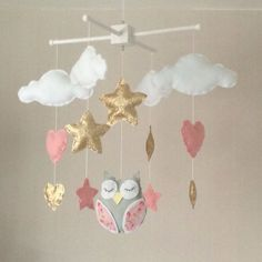 Owl, clouds, hearts and stars baby crib mobile. An ideal gift for a new babys nursery or for room decor in an older childs bedroom. This mobile consists of four white clouds, four hearts in pale pink and gold , five stars in sparkling gold and pink and a beautiful grey sleeping owl with pink patterned wings in the centre. The elements are suspended with white thread from either a natural wood or a white wooden mobile hanger. Each element is created with felt and entirely hand sewn. The…