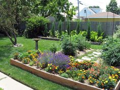 A short stone path terminates at a wood planter box in this small backyard garden.
