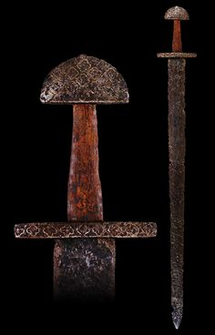 A Rare Viking Sword, 10th/11th century In excavated condition, with broad pattern-welded blade of flattened hexagonal section, iron hilt comprising cross-guard of tapering rectangular section and slender pommel of 'tea cozy' form, each inlaid with a...