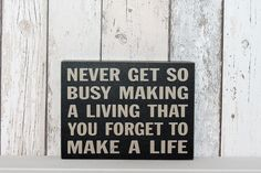 Black block sign with inspirational quote. 'Never get so busy making a living...'