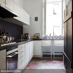 Die nostalgischen Sechseck-Fliesen in Rot- und Beigetönen hauchen der schmalen Küche einen individuellen Charakter ein. Durch den alten Holzschrank und die  …