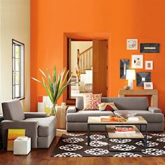 orange walls. grey furniture. I like the idea of neutral furnishings, then changing out the pops of color on the accessories and the walls as my mood changes... :]