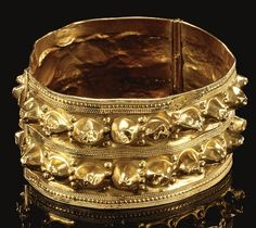A GOLD BRACELET, PERSIA of broad circular form, double-hinged, decorated with two continuous bands of raised repoussé conical bosses between raised ropework borders, 13th-14th century or later 6.3cm. diam.