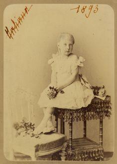 Princesa Tatiana Constantinovna. Ela está sentada em uma mesa decorada com borlas com os pés descansando em uma cadeira ao lado dela para a esquerda. Ela está segurando uma flor e há flores na cadeira e mesa. A fotografia é assinada e datada com seu nome.