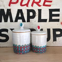 A handmade and wheel thrown jar or canister, perfect for storing flour, sugar, tea, or anything. Thrown on a pottery wheel, I sponged on a turquoise blue and red polka dot bottom pattern, then added a thumbprint of red then turquoise to each side of the lid's knob.