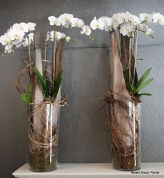 Reception area pieces for the Senator Hotel lobby with white phalaenopsis orchids, palm branches, moss and curly willow.
