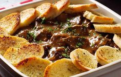 Enjoy a slow-cooked casserole of melt-in-your-mouth beef in a rich gravy topped with golden slices of seasoned bread.