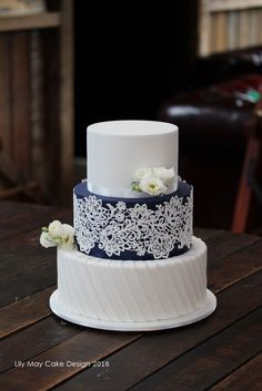 Beautiful navy blue & crisp white wedding cake with edible lace detail.