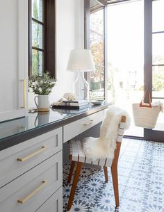 A long home office features a light gray built in desk adorned with brushed brass pulls topped with charcoal gray quartz and lined with a white woven chair placed atop a white and gray cement tile floor.