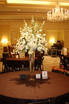 large centerpiece of white hydrangeas, larkspur, orchids and spirea designed by tina barrera