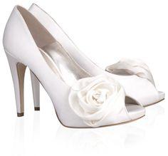 Pura Lopez Carmen- Zapatos de novia de Pura López realizados en raso blanco roto, con tacón alto, plataforma cubierta y flor de raso adornando el lateral.