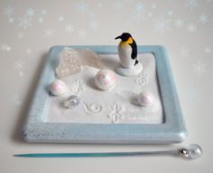 Fresh snow has fallen and this emperor penguin is ready to play! He loves making snowballs and rolling them around in the snow. This miniature desktop zen garden lets you display your love for the season with an Emperor Penguin set in a snowy landscape. The glass base has been painted in blue, white, and metallic silver. The two Quartz Crystals even look like ice! Draw designs in the snow (sand) with the mini stylus and rearrange the miniatures! Use as many or as little as you like. Great…