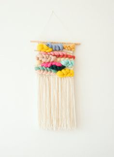 Rainbow Woven Wall Hanging with a lot of colorful roving and gold ribbon