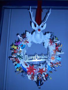 Kerstkrans gemaakt van rommeltjes uit de speelgoedschuif! Eerst een oude krans omwikkelen met witte ducttape, dan een kerstslinger rondwikkelen en vastzetten met een lijmpistool en vervolgens een heleboel kersttaart- en surprise-eitjesfiguurtjes vastkleven! Leuk voor aan de voordeur!