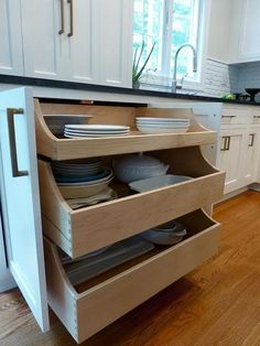 Kitchen Pull-out Drawers. Underneath you can open up the two doors to reveal three large pull out drawers that house my large serving dishes. No more being on your hands and knees trying to pull them out from the bottom of the cabinets, I literally can open the drawers up and see what I need. The sides of the pullouts are staggered so you can see in easily too. The countertop cabinet doors fold back onto themselves to tuck out of the way Kate Abt Design. #KitchenPullOutDrawers #PullOut...